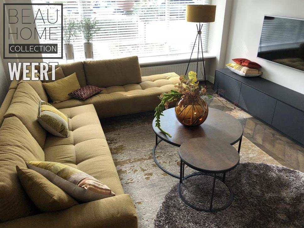 Woonkamer met hoekbank in geel stof, keramiek salontafel set, mooie karpetten en zwart houten tv-dressoir